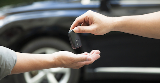 hands giving and receiving car key