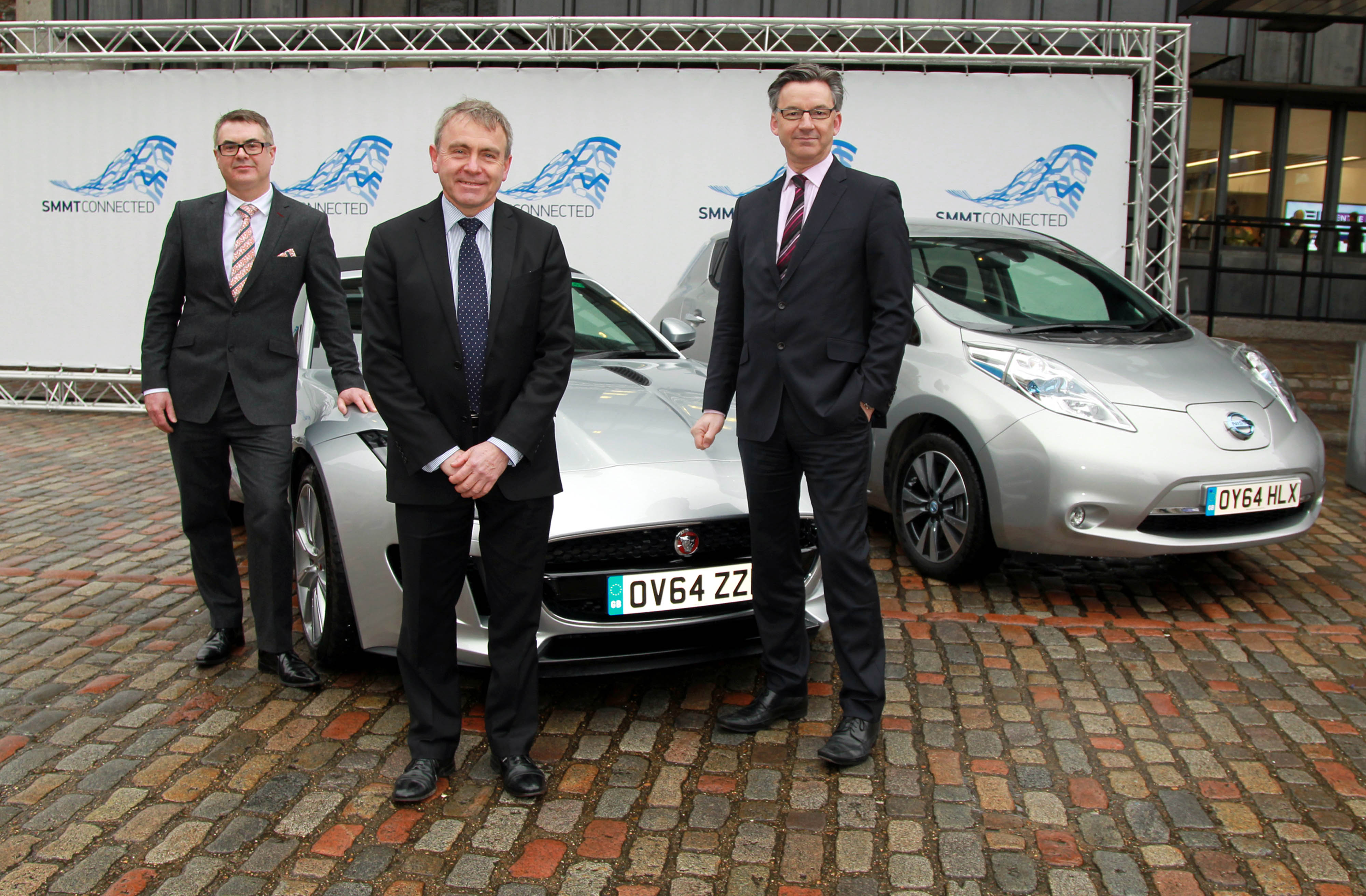 EDITORIAL USE ONLY Mike Bell, Global Connected Car Director at Jaguar Land Rover, Robert Goodwill MP, Parliamentary Under-Secretary of State and Mike Hawes, SMMT Chief Executive, with a Jaguar F-type and a Nissan Leaf, ahead of the SMMTConnected conference at Queen Elizabeth II Conference Centre, London, as it is announced that the automotive industry's innovation in connected and autonomous cars is expected to create 320,000 UK jobs and generate £51 billion for the UK economy. PRESS ASSOCIATION Photo. Picture date: Thursday March 26, 2015. Photo credit should: Sean Dempsey/PA Wire